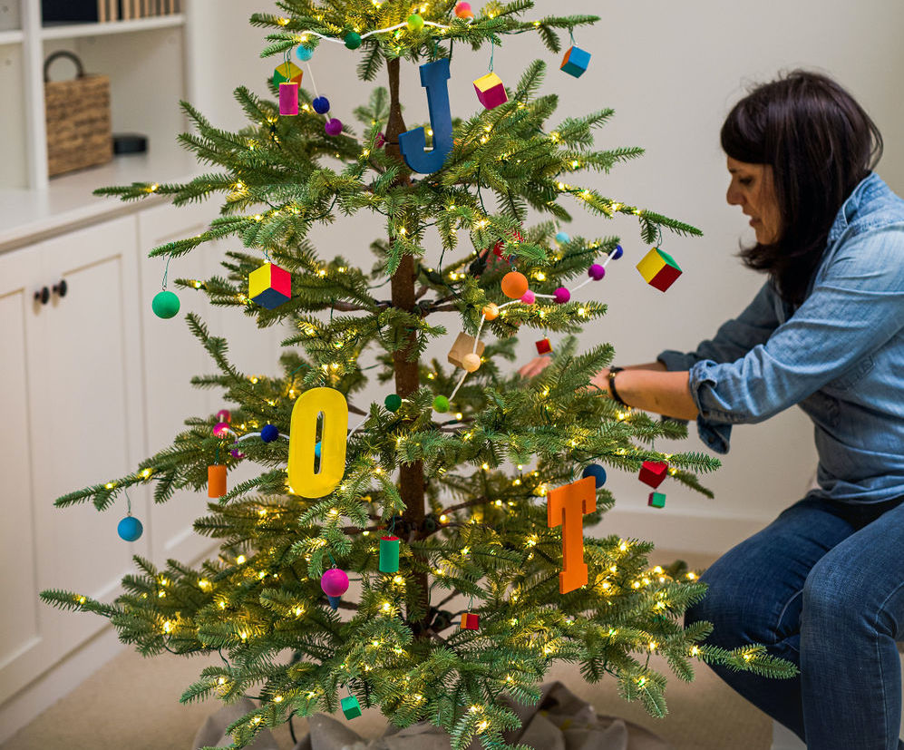woman decorating christmas tree with whimsical themed decorations