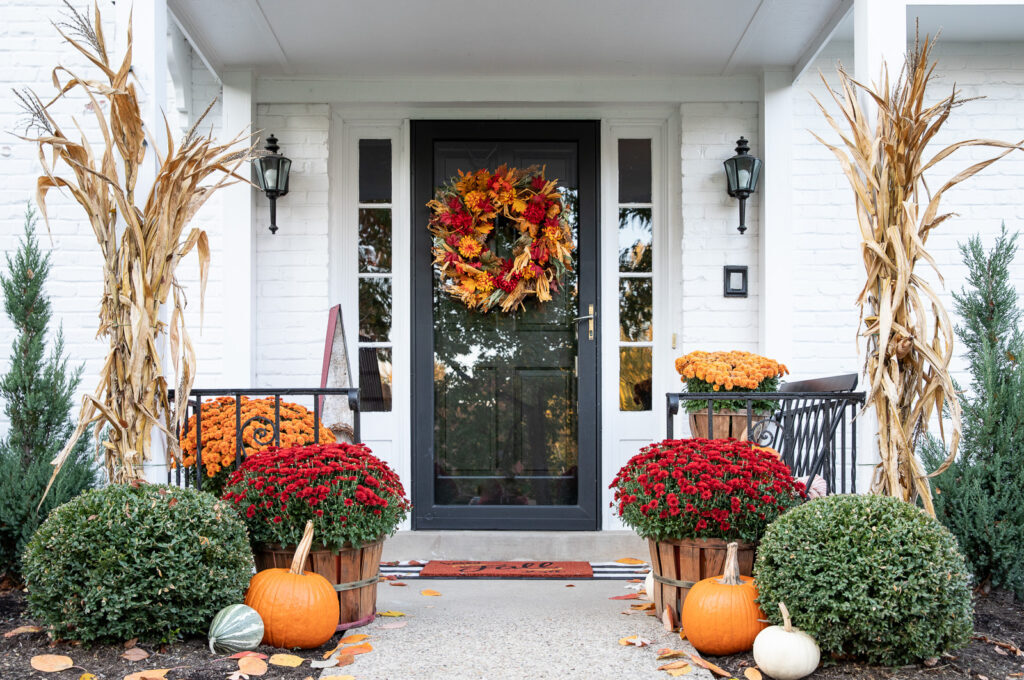 fall wreath, flowers, and pumpkins on front porch