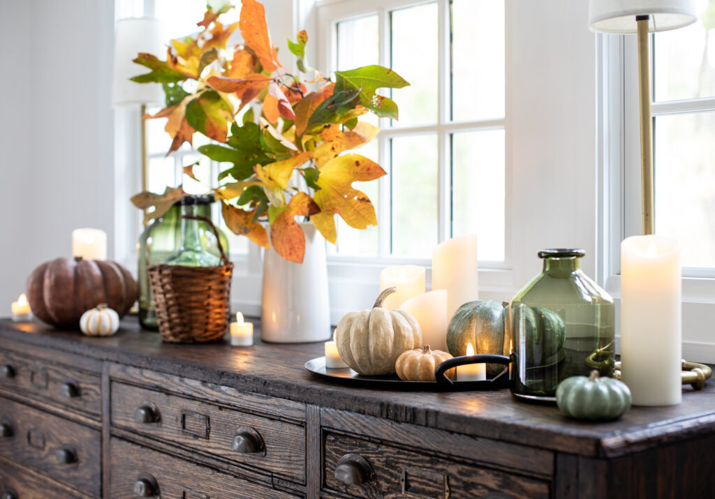 sideboard with faux pumpkins, candles, and fall foliage