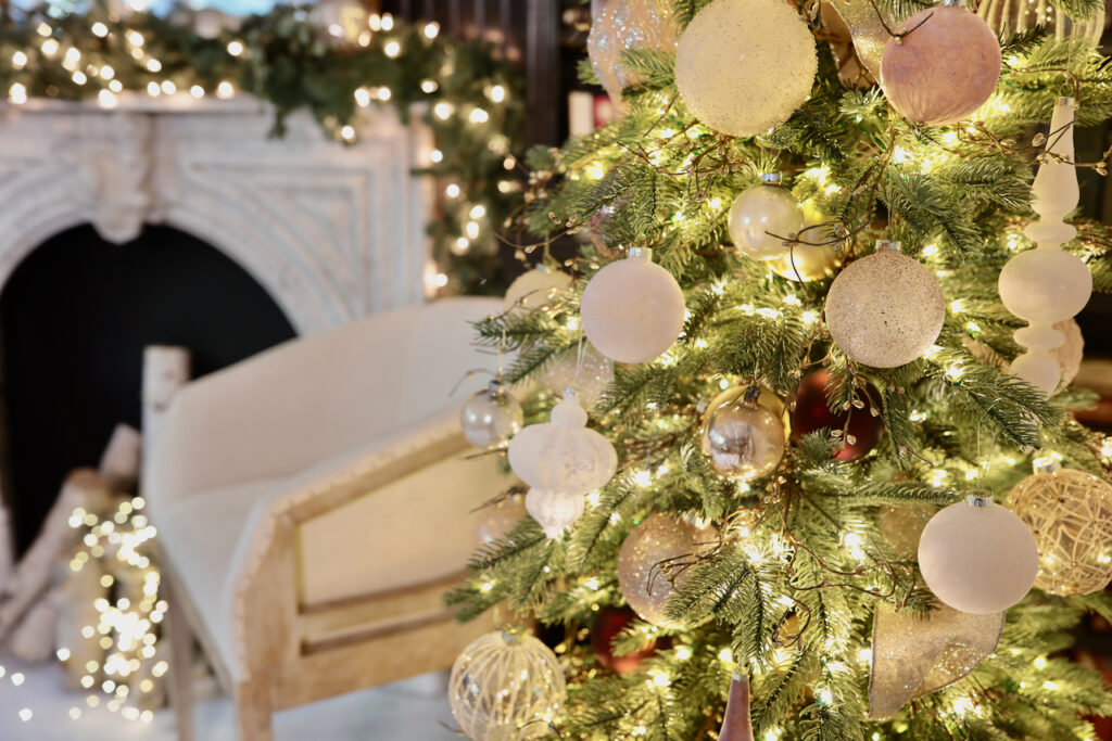 Close-up shot of a Christmas tree with blush, white, and, metallic ornaments