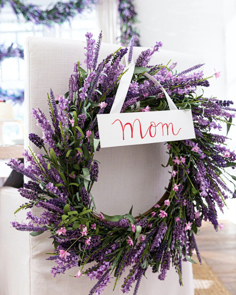 Balsam Hill Provencal Lavender wreath with name card hung on the back of a white dining chair
