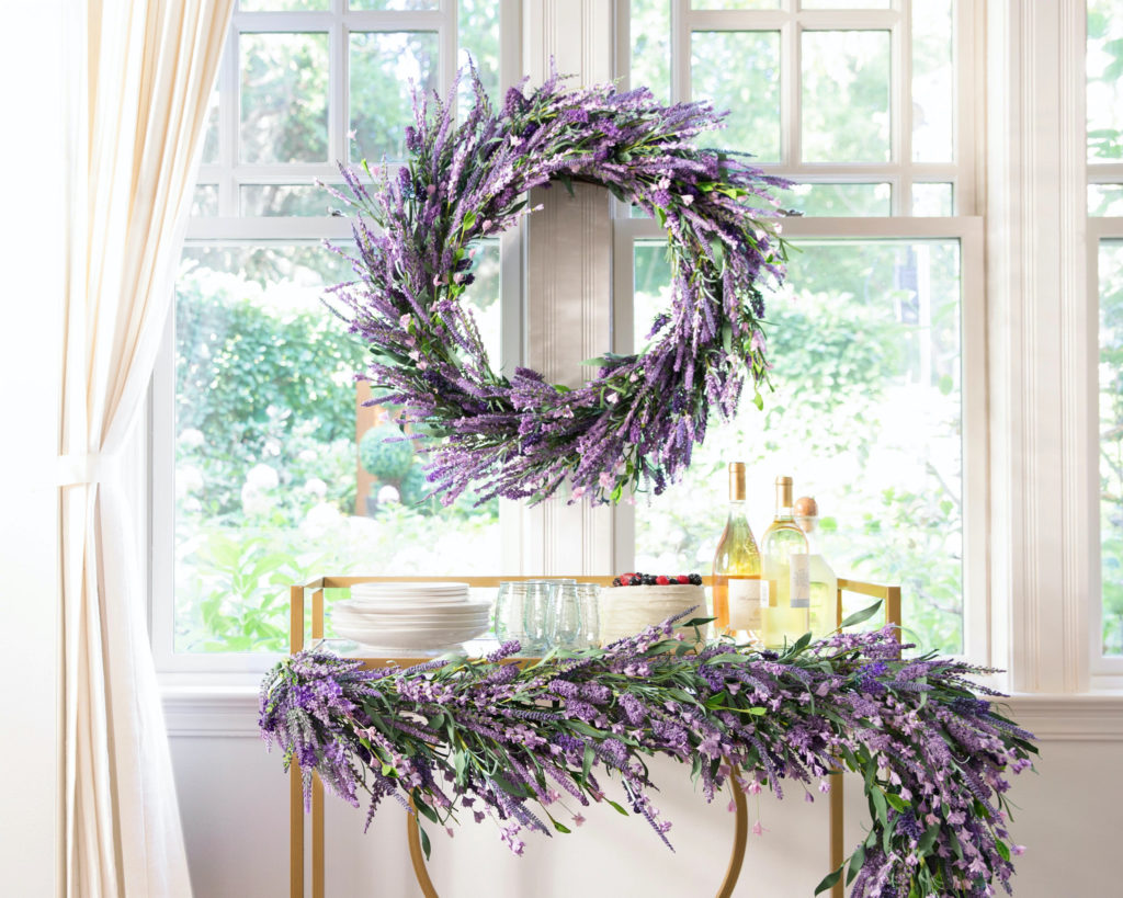 Dessert and bar cart decorated with Balsam Hill Provencal Lavender Garland and a matching wreath hung on the window behind it
