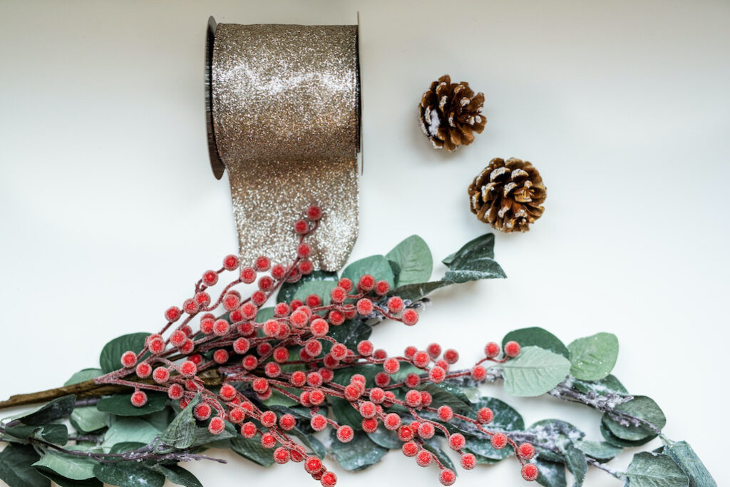frosted red berries, pinecones, eucalyptus picks, and ribbon