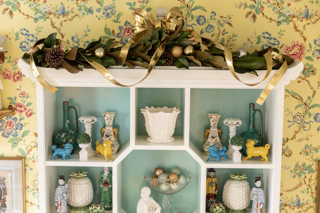 christmas decorating with magnolia garland on display cabinet