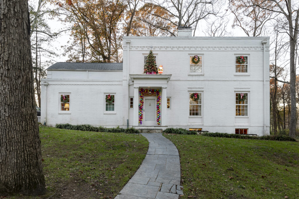 white house decorated with christmas tree and wreaths