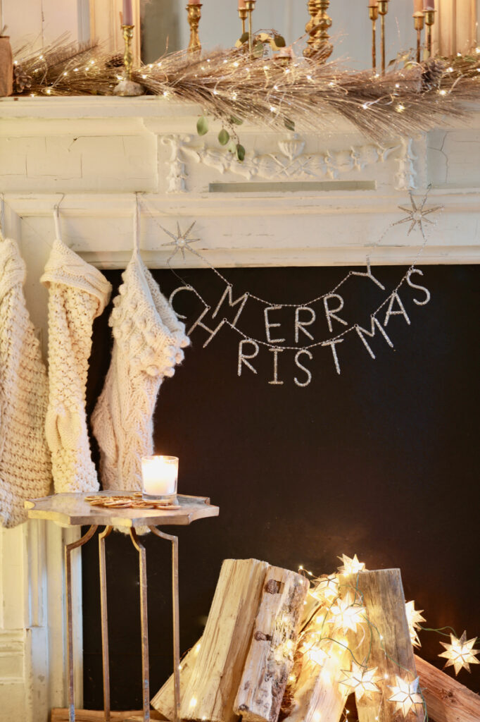 merry christmas garland and stockings hanging on mantel