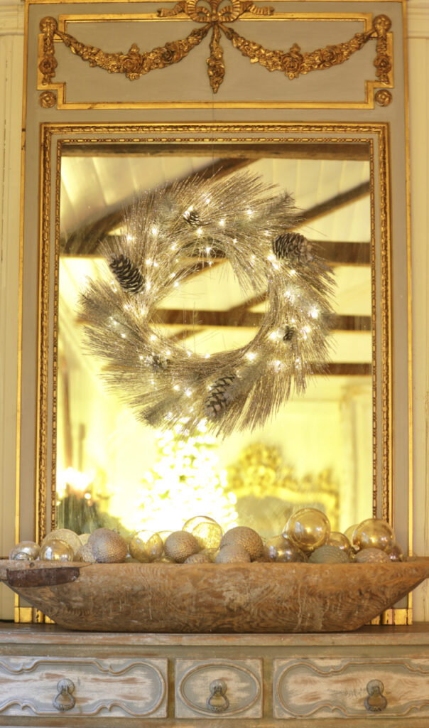 pre-lit champagne pine wreath on a vintage mirror