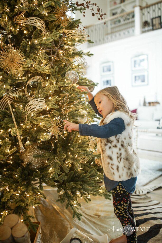 child beside christmas tree