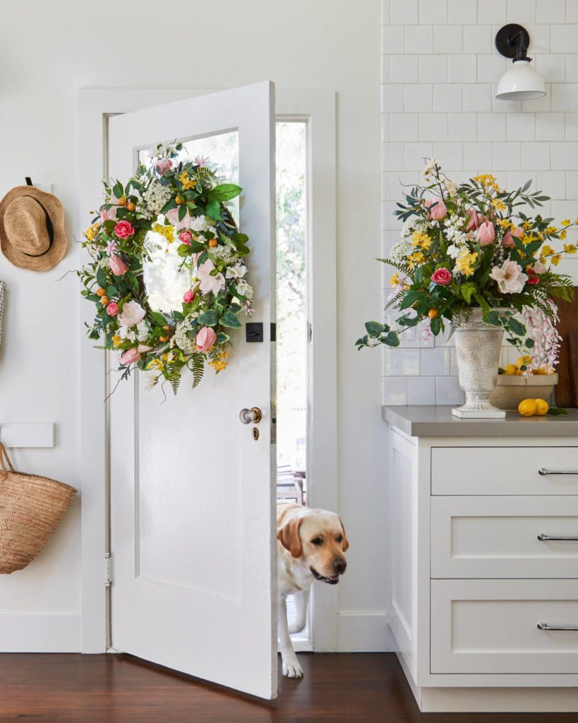 Balsam Hill Spring in Bloom floral wreath hung inside door with floral arrangement on countertop