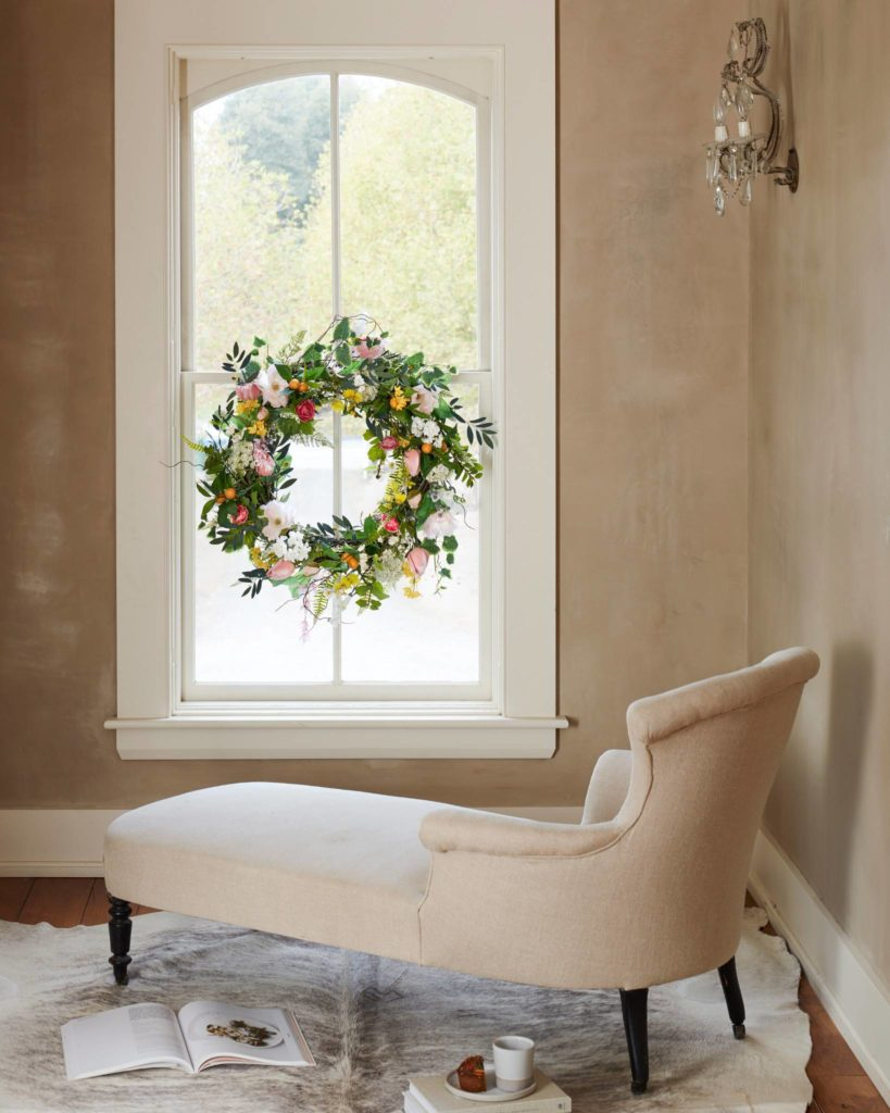 Balsam Hill Spring in Bloom Wreath hung on a window in a reading nook