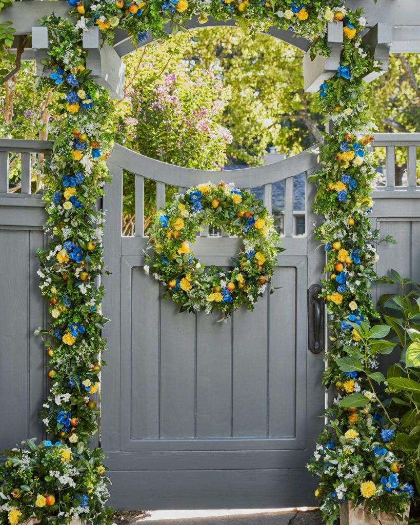 Balsam Hill Outdoor Summer Breeze wreath, garland, and potted foliage on gate