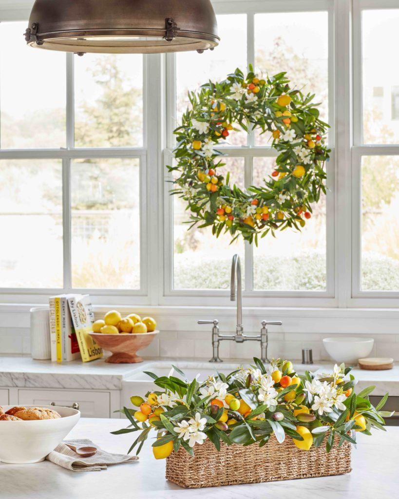 Balsam Hill Villa Cucina wreath hung on window above kitchen sink with matching floral arrangement on kitchen island countertop