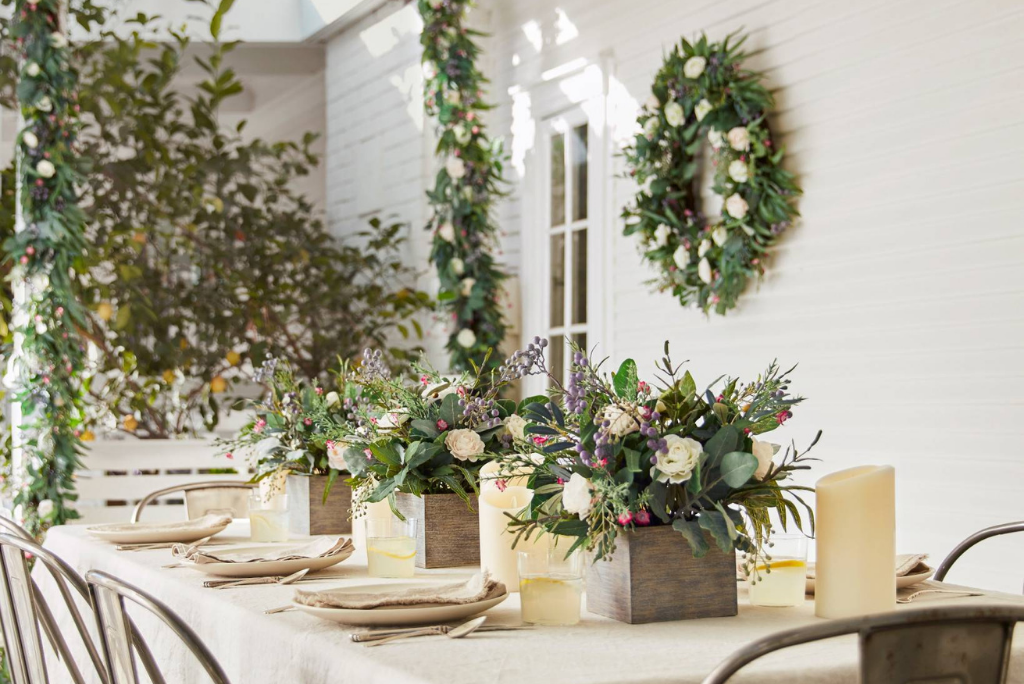 Balsam Hill Marseille Meadow wreath and garland on patio wall with matching floral arrangements as table centerpiece
