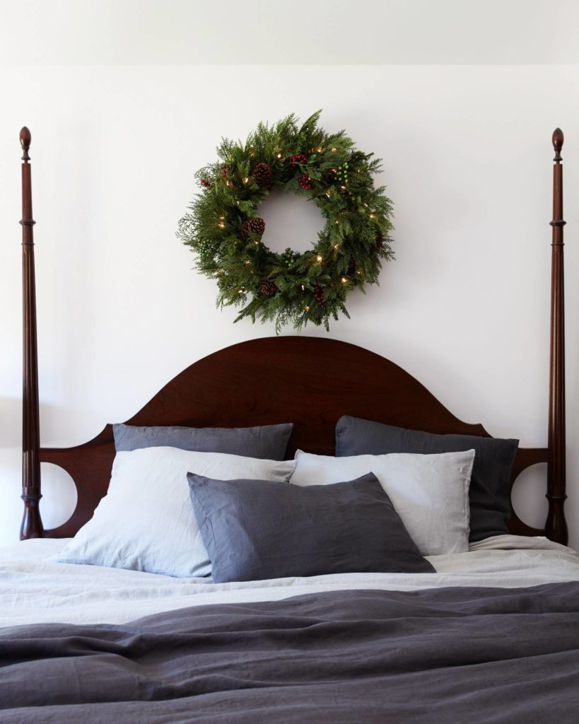 Balsam Hill Winter Evergreen wreath hung on the wall above bed head board