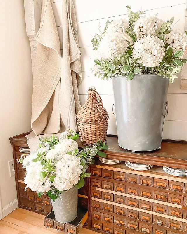 Balsam Hill Nantucket Hydrangea artificial floral arrangement beside a similar fresh flower arrangement