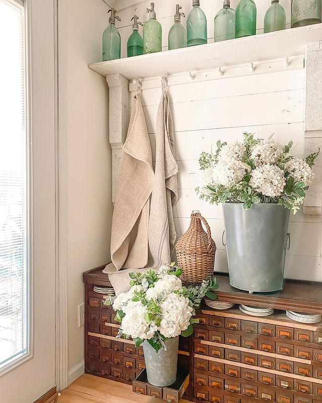 Balsam Hill Nantucket Hydrangea artificial floral arrangement beside a similar fresh flower arrangement on a cupboard