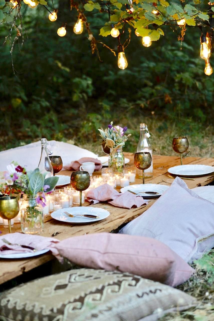 Low outdoor table decorated with votives, fresh flowers, and pillows as seats