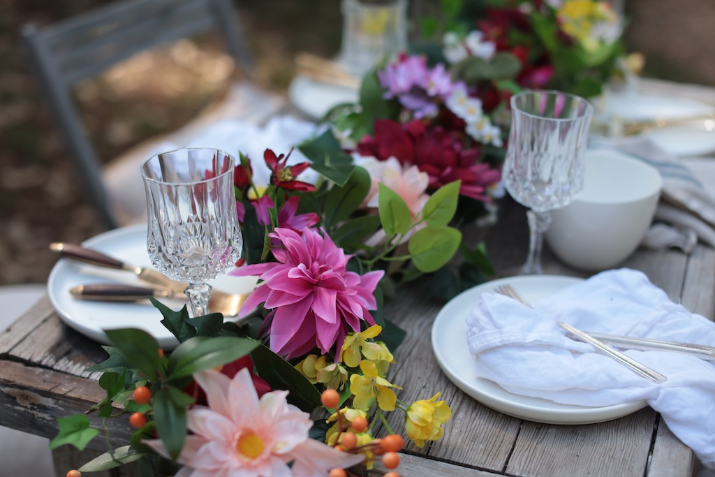 Plates, napkins, gold flatware, and gold glasses on top of table with Balsam Hill artificial floral garland as centerpiece