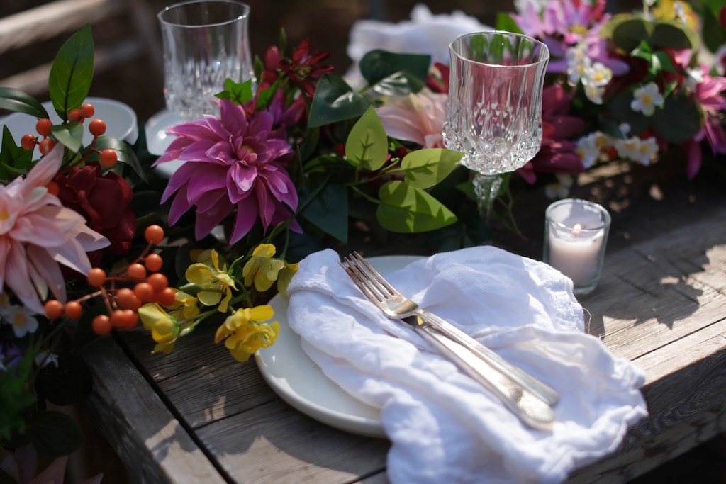 Outdoor table setting with crystal glasses, votives, and Balsam Hill Midsummer Medley artificial floral garland