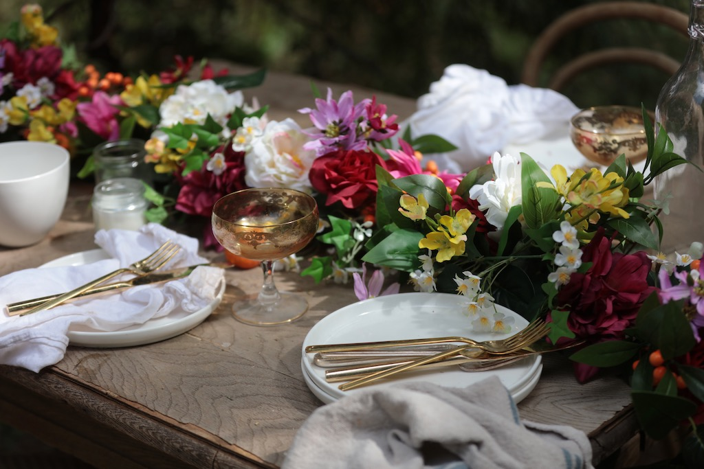 Outdoor table decorated with Balsam Hill artificial floral garland and place settings with gold flatware and glasses