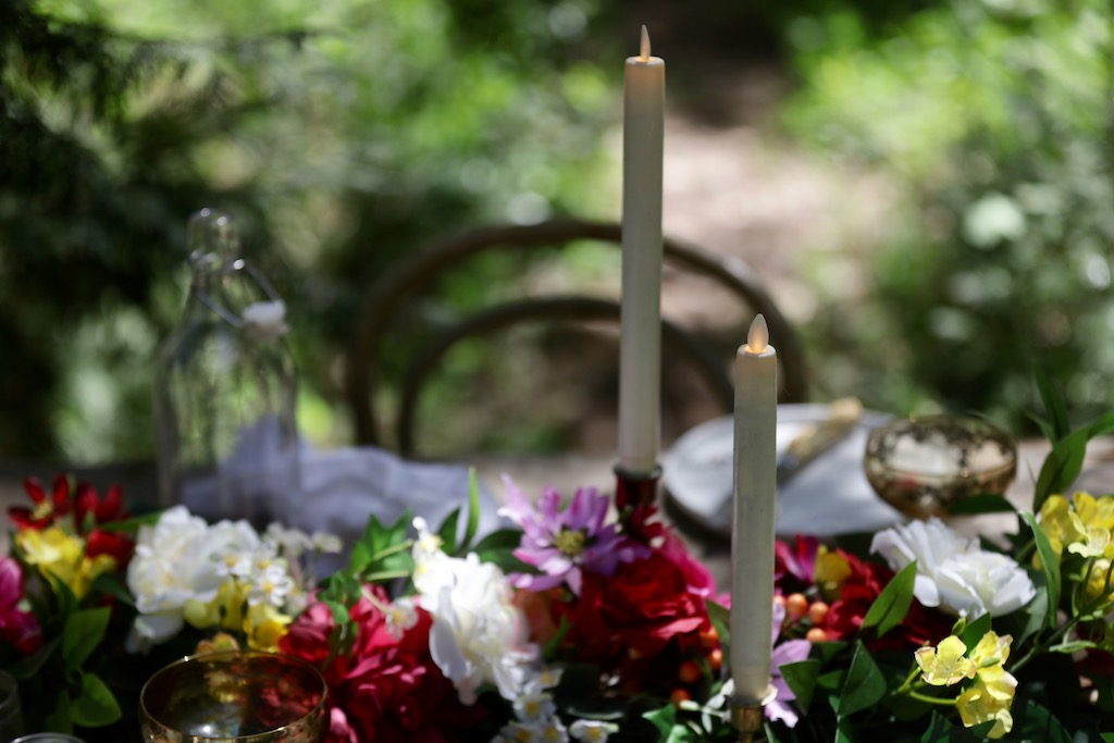 Balsam Hill Miracle Flame LED candles with artificial floral garland on top of an outdoor dining table