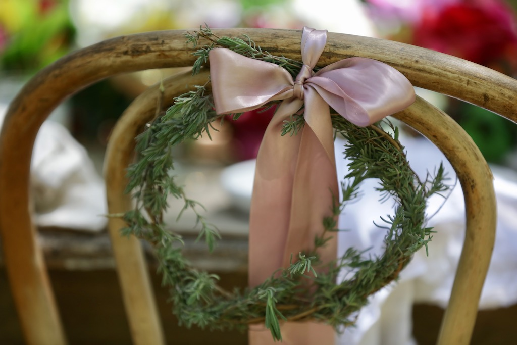 Handmade wreaths with ribbon tied on the back of a chair