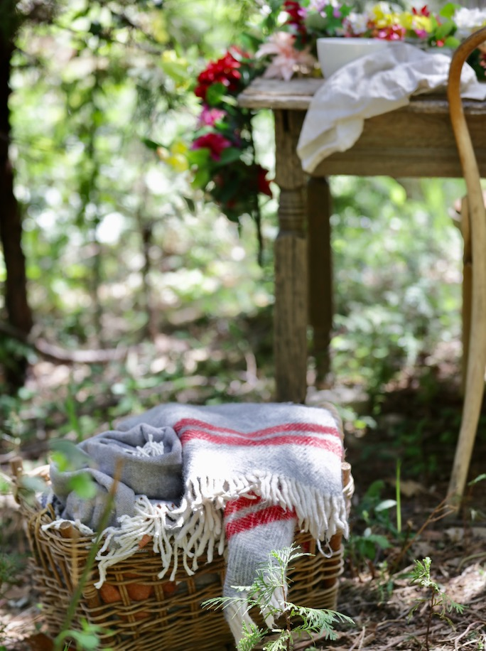 A basket of throws and blankets for guests when entertaining outdoors