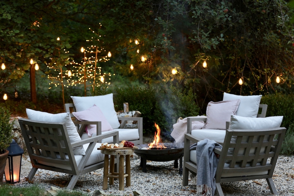 Outdoor fire pit with cushioned lounge chairs