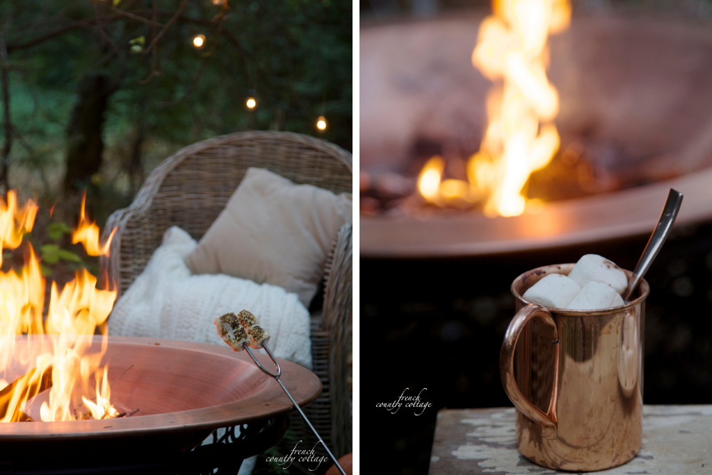 Marshmallows on roasting forks and hot cocoa with marshmallows by an outdoor fire pit