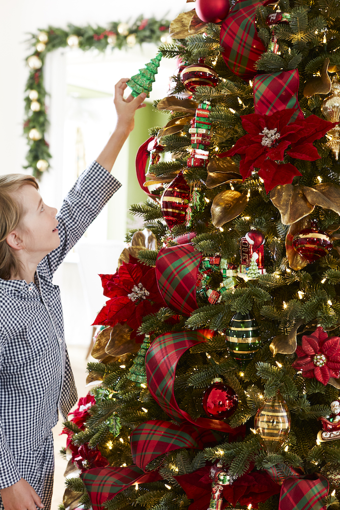 Little boy decorating an artificial Christmas tree with a green tree ornament