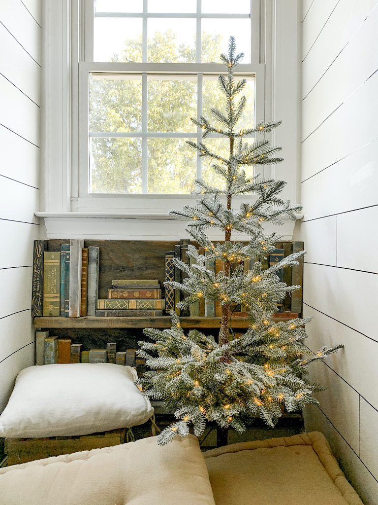 Pre-lit Balsam Hill Frosted Alpine Balsam Fir with pillows on the floor inside a reading nook