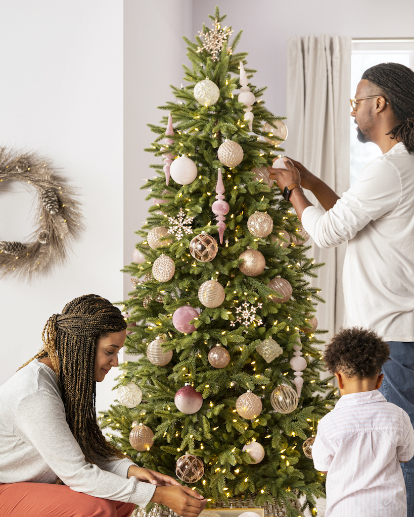 Family decorating a Balsam Hill Christmas tree