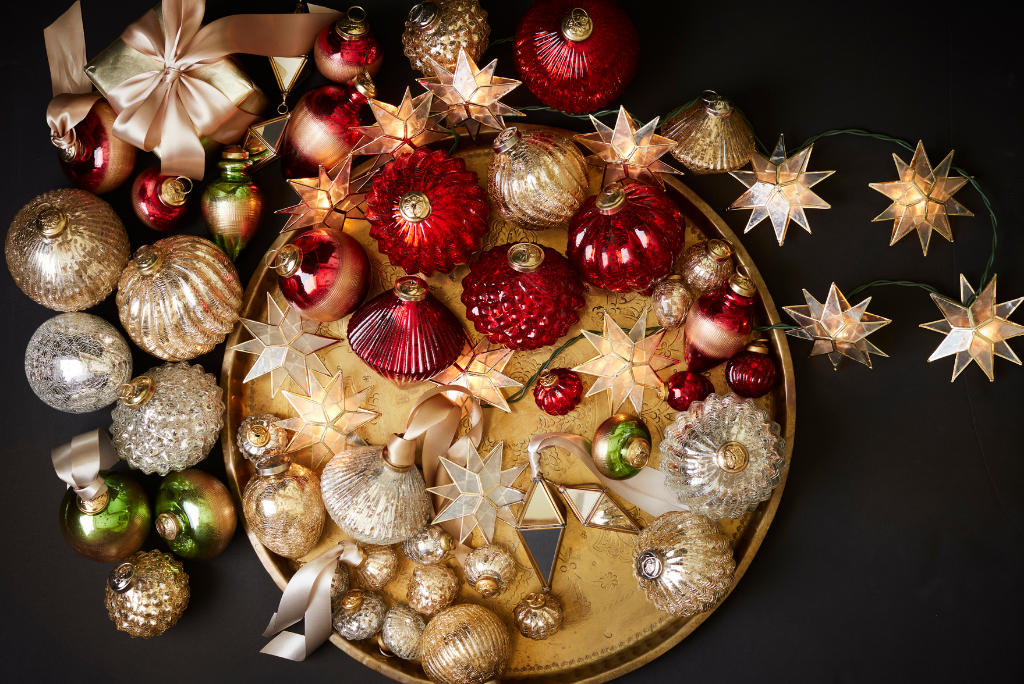 An assortment of Balsam Hill glass and capiz ornaments in  red, gold, silver, and green