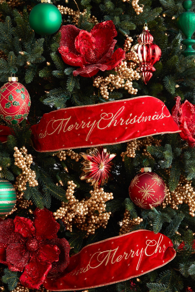 Balsam Hill Christmas tree theme ideas featuring red velvet ribbon, poinsettia picks, red ornaments, and small gold berries